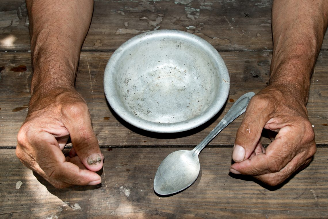 hands the poor old man's and empty bowl on wood background. The concept of hunger or poverty. Selective focus. Poverty in retirement.Homeless.  Alms